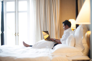 man in bed on laptop