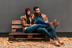 ouple bonding to each other while sitting on the wooden pallet with grey wall in the background and fallen leaves on the floor